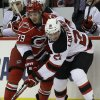 Carolina Hurricanes\' Patrick Dwyer (39) and New Jersey Devils\' Andrei Loktionov (21), of Russia, chase the puck during the second period of an NHL hockey game in Raleigh, N.C., Thursday, March 21, 2013. (AP Photo/Gerry Broome)