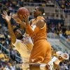 Photo - Texas' Damarcus Croaker, right, drives to the basket as West Virginia's Brandon Watkins defends during the first half of an NCAA college basketball game, Monday, Jan. 13, 2014, in Morgantown, W.Va. (AP Photo/Andrew Ferguson)
