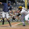Photo - San Diego Padres' Seth Smith, left, avoids the tag by Pittsburgh Pirates starting pitcher Charlie Morton as he scores from third on a wild pitch by Morton to Padres' Yonder Alonso in the fifth inning of the baseball game on Sunday, Aug. 10, 2014, in Pittsburgh. (AP Photo/Keith Srakocic)