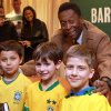 Photo - Brazilian soccer star Pele, poses for a photo with fans, from left, Lucas LaFleur, Ethan Kaplowitzs and  Lorenzo Gutierrez Baker, during an appearance at Barnes & Noble to signs copies of his book