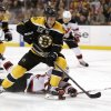 Photo - Boston Bruins' Gregory Campbell cuts pas sprawling New Jersey Devils defenseman Eric Gelinas during the second period of an NHL hockey game in Boston, Saturday, Oct. 26, 2013. (AP Photo/Winslow Townson)
