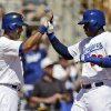 Los Angeles Dodgers\' Yasiel Puig, right, is met at the plate by Andre Ethier after Puig\'s two-run home run against the Oakland Athletics during the first inning of a spring training baseball game on Tuesday, March 19, 2013 in Glendale, Ariz. (AP Photo/Marcio Jose Sanchez)