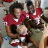 FullbackTrey Millard (33) and running back Damien Williams sign pose with Adalyn Smith, one, as they sign autographs during fan appreciation day for the University of Oklahoma Sooner (OU) football team at Gaylord Family-Oklahoma Memorial Stadium in Norman, Okla., on Saturday, Aug. 3, 2013. Photo by Steve Sisney, The Oklahoman