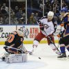 New York Islanders goalie Evgeni Nabokov (20) stops a shot on goal by Columbus Blue Jackets\' Artem Anisimov (42) as Islanders\' Travis Hamonic (3) defends from behind in the first period of an NHL hockey game on Sunday, March 23, 2014, in Uniondale, N.Y. (AP Photo/Kathy Kmonicek)