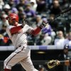 Photo -   Arizona Diamondbacks Chris Young hits a two-run home run in the first inning of a baseball game against the Colorado Rockies on Sunday, April 15, 2012 in Denver. (AP Photo/Chris Schneider)