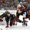 Photo - Phoenix Coyotes' Antoine Vermette (50) and Calgary Flames' Lee Stempniak (22) get tangled up as they send Coyotes' Connor Murphy (5) to the ice in front of Coyotes goalie Thomas Greiss (1), of Germany, during the first period of an NHL hockey game, Tuesday, Jan. 7, 2014, in Glendale, Ariz. (AP Photo/Ross D. Franklin)