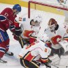 Photo - Montreal Canadiens' Rene Bourque, left, scores against Calgary Flames goaltender Reto Berra, right, as Flames' Mikael Backlund (11) and Ladislav Smid defend during the second period of an NHL hockey game Tuesday, Feb. 4, 2014, in Montreal. (AP Photo/The Canadian Press, Graham Hughes)