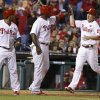 Photo - Philadelphia Phillies' Ryan Howard, center, gives Cody Asche, right, a high five with Marlon Byrd, left, score on the double by Domonic Brown during the seventh inning of a baseball game against the Cincinnati Reds, Saturday, May 17, 2014, in Philadelphia. The Phillies win 12-1. (AP Photo/Chris Szagola)