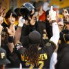 Photo - Pittsburgh Pirates' Andrew McCutchen (22) celebrates with teammates in the dugout after hitting a two-run home run off Milwaukee Brewers starting pitcher Yovani Gallardo during the first inning of a baseball game in Pittsburgh, Thursday, April 17, 2014. (AP Photo/Gene J. Puskar)