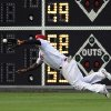 Photo - Philadelphia Phillies right fielder Marlon Byrd dives and catches a ball hit by San Francisco Giants' Hunter Pence during the first inning of a baseball game on Monday, July 21, 2014, in Philadelphia. (AP Photo/Michael Perez)