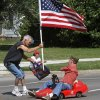 A citizen along the parade route comes to the aid of this veteran driving a miniature car in the parade after strong winds separated the American flag from its base on the car. The man retrieved the flag from the road and ran to the car to reinstall it. Del City and eastern Oklahoma County residents lined S. Sunnylane Road to show their support for America\'s military, applauding and cheering participants who marched and rode in the city\'s Armed Forces Day Parade on Saturday morning, May, 19, 2012. The parade worked its way along the Del City route for a little more than an hour. Photo by Jim Beckel, The Oklahoman