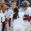 Photo - Arizona State's Krista Donnenwirth (11), right, is greeted by her teammates at home plate after hitting a three-run home run in the second inning during game 1 of the Women's College World Series championship softball final between the University of Florida and Arizona State University at ASA Hall of Fame Stadium in Oklahoma City, Monday, June 6, 2011. Photo by Nate Billings, The Oklahoman