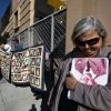 Survivor Angie Story, 67, right, holds on to a picture of
