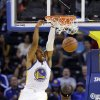 Photo - Golden State Warriors' Andre Iguodala (9) dunks in front of Sacramento Kings' DeMarcus Cousins (15) during the first half of an NBA preseason basketball game Monday, Oct. 7, 2013, in Oakland, Calif. (AP Photo/Marcio Jose Sanchez)