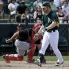 Photo - Oakland Athletics shortstop Jed Lowrie, right, reacts after striking out as Cincinnati Reds catcher Cory Miller looks on during the third inning of a spring exhibition baseball game in Phoenix, Tuesday, March 25, 2014. (AP Photo/Chris Carlson)
