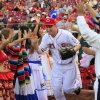 Photo -   Cincinnati Reds' Todd Frazier high-fives dancers from Central and South America as he runs onto the field at the start of a baseball game against the Houston Astros, Friday, Sept. 7, 2012, in Cincinnati. The costumed dancers were part of Hispanic Heritage Night events at the ballpark. (AP Photo/Al Behrman)