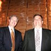 Photo - Above: Keith R. Schroeder, chief financial officer, and Robert A. Snyder, president and CEO, stand in front of boxes of bathroom tissue at Orchids Paper Products.
