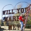 "Right: Yukon city worker Julia Puckett strings Christmas lights on the ""Will you marry me?"" sign at Chisholm Trail Park. Photo by Paul B. Southerland, The Oklahoman"