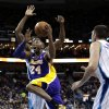 Photo - Los Angeles Lakers guard Kobe Bryant (24) drives to the basket past New Orleans Hornets forward Al-Farouq Aminu, behind, during the first half of an NBA basketball game in New Orleans, Wednesday, March 6, 2013. (AP Photo/Gerald Herbert)