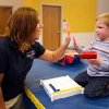 Jake Linn (right) travels to the J. D. McCarty Center in Norman each week from Prague, Oklahoma, for outpatient therapy. Three-year-old Jake receives physical, occupational and speech therapy. Jake's mom, Susan Linn, says the drive is a small sacrifice for the great rewards her kids get from being at the McCarty Center. Certified Occupational Therapy Assistant Mikki Patten gives Jake a high five for his successful completion of an eye/hand coordination exercise. Community Photo By: Greg Gaston Submitted By: Greg, Norman