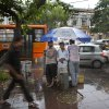 Indian commuters walk home in the rain as others take shelter under the umbrella of a mobile water drinking carriage in New Delhi, India, Monday, May 23, 2016. After days of relentless summer heat, storm accompanied by short spells of rain brought relief to the Indian capital. The main summer months in India April, May and June are always excruciatingly hot across most of the country, before monsoon rains bring cooler temperatures. (AP Photo/Manish Swarup)