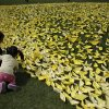 Photo - A girl with a man puts a paper ship she made to pay tribute to the victims and missing passengers of the sunken ferry Sewol at a group memorial altar in Seoul, South Korea, Wednesday, May 7, 2014. The ferry disaster left more than 200 people dead, with others still missing. Government and civilian divers are fighting rapid currents as they try to retrieve the remaining bodies. (AP Photo/Lee Jin-man)