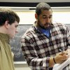 Photo - FILE - In this March 27, 2013, file photo, Penn State offensive lineman John Urschel, right, helps freshman Zachary Middleton with a math problem after teaching his trigonometry and analytical geometry class in State College, Pa. The 6-foot-3, 315-pound Urschel is one of 15 guards invited to the NFL scouting combine in Indianapolis. (AP Photo/York Daily Record/Sunday News, Chris Dunn) YORK DISPATCH OUT