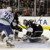 Photo - Los Angeles Kings goalie Jonathan Quick (32) deflects the puck with defenseman Drew Doughty (8) as Vancouver Canucks center Mike Santorelli (25) moves in in the first period of an NHL hockey game in Los Angeles, Monday, Jan. 13, 2014. (AP Photo/Reed Saxon)