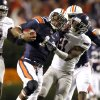 Photo - Auburn quarterback Nick Marshall, left, stiff arms Florida Atlantic defensive back D'Joun Smith as he carried the ball for first down during the first half of an NCAA college football game on Saturday, Oct. 26, 2013, in Auburn, Ala. (AP Photo/Butch Dill)