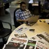 "An Egyptian journalist works at the editorial room of Al-Masry Al-Youm daily newspaper next to copies of Egypt's most prominent newspapers running black background front pages with Arabic that reads, ""no to dictatorship, tomorrow free newspapers will obscure to protest the freedom\'s restrictions,"" and a picture of a man wrapped in newspapers with his feet cuffed, in Cairo, Egypt, Monday, Dec. 3, 2012. Eleven Egyptian newspapers are planning to suspend publication on Tuesday to protest against President Mohammed Morsi\'s decision to call a constitution referendum on 15 December. (AP Photo/Nasser Nasser)"