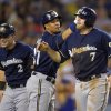 Photo - Milwaukee Brewers' Mark Reynolds, right, is congratulated by Carlos Gomez, center, and Scooter Gennett after scoring on a double by Lyle Overbay during the eighth inning of a baseball game against the Los Angeles Dodgers, Friday, Aug. 15, 2014, in Los Angeles. (AP Photo/Mark J. Terrill)