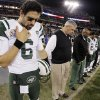 Photo - New York Jets quarterback Mark Sanchez (6) and head coach Rex Ryan bow their heads during a moment of silence for the victims of the Sandy Hook Elementary School shootings in Newtown, Conn., before an NFL football game against the Tennessee Titans, Monday, Dec. 17, 2012, in Nashville, Tenn. (AP Photo/Wade Payne)
