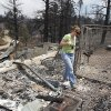 Teresa Jiles walks through the remains of her home that was destroyed by the High Park Fire in the Glacier View residential area near Livermore, Colo., on Monday, July 2, 2012. The last evacuees from the fire in have been allowed to return home as crews fully contained the136-square-mile wildfire that killed one resident and destroyed 259 houses. (AP Photo/Ed Andrieski) ORG XMIT: COEA102