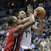 Minnesota Timberwolves\' Derrick Williams, right, eyes the basket for a shot as Miami Heat\'s Chris Bosh defends in the first half of an NBA basketball game Monday, March 4, 2013, in Minneapolis. (AP Photo/Jim Mone)