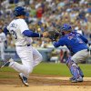 Photo - Los Angeles Dodgers' Adrian Gonzalez, left, starts to slide into home, before being tagged out by Chicago Cubs catcher Welington Castillo during the first inning of a baseball game, Friday, Aug. 1, 2014, in Los Angeles. (AP Photo/Mark J. Terrill)