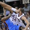 New Jersey Nets center Brook Lopez, right, and forward Derrick Favors blocks a shot by Oklahoma City Thunder guard James Harden, left, during the first quarter of an NBA basketball game Wednesday, Dec. 1, 2010, in Newark, N.J. (AP Photo/Bill Kostroun)