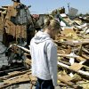 TORNADO DAMAGE, HOUSE: Tressie Gilmore, 25, walks past the remains of her family\'s home on May,11, 2008, following a tornado that hit the area on Saturday. By John Clanton, The Oklahoman ORG XMIT: KOD