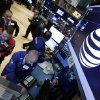 Photo - Traders gather at the post that handles AT&T on the floor of the New York Stock Exchange Monday, May 19, 2014. Priming itself for the age of Internet-delivered video, AT&T Inc. said it would buy DirecTV for $48.5 billion in cash and stock, or $95 per share. (AP Photo/Richard Drew)