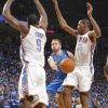 Jose Barea (11) of Dallas passes the ball between Oklahoma City\'s Serge Ibaka (9) andOklahoma City\'s Kevin Durant (35) during game 3 of the Western Conference Finals of the NBA basketball playoffs between the Dallas Mavericks and the Oklahoma City Thunder at the OKC Arena in downtown Oklahoma City, Saturday, May 21, 2011. Photo by Chris Landsberger, The Oklahoman