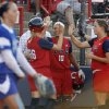 Photo - U.S. / UNITED STATES: The United States' Caitlin Lowe (26) is congratulated by teammates, including Brittany Rogers (10) and Stacey Nelson (42), as pitcher Leslie Malerich of Italy walks back to the circle after Lowe scored in the first inning during the game between the USA and Italy in the World Cup of Softball at ASA Hall of Fame Stadium in Oklahoma City, Friday, July 17, 2009. By Nate Billings, The Oklahoman ORG XMIT: KOD