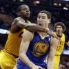 Photo - Golden State Warriors' Klay Thompson, right, tries to get past Cleveland Cavaliers' C.J. Miles during the first quarter of an NBA basketball game Sunday, Dec. 29, 2013, in Cleveland. (AP Photo/Tony Dejak)