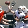 Oklahoma State quarterback Wes Lunt, center, throw under pressure from defenders Davidell Collins (98) and Tyler Johnson (40) during a spring NCAA college football game in Stillwater, Okla., Saturday, April 21, 2012. (AP Photo/Sue Ogrocki) ORG XMIT: OKSO102