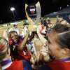 Photo - Rhea Taylor, left holding the trophy, and other members of Team USA celebrate a 3-0 win over Australia in the championship game of the World Cup of Softball at ASA Hall of Fame Stadium on Monday.  Photo by Nate Billings, The Oklahoman