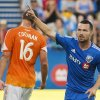 Photo - Montreal Impact's Jack McInerney, right, celebrates after scoring against the Houston Dynamo as Dynamo's A.J. Cochran looks on during the first half of an MLS soccer game in Montreal, Sunday, June 29, 2014. (AP Photo/The Canadian Press, Graham Hughes)