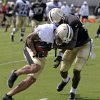 New Orleans Saints wide receiver Kenny Stills, left, carries against cornerback A.J. Davis during their NFL football training camp in Metairie, La., Tuesday, July 30, 2013. (AP Photo/Gerald Herbert)