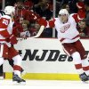 Photo - Detroit Red Wings center Joakim Andersson, right, of Sweden, and left wing Drew Miller celebrate a goal by Andersson during the second period of an NHL hockey game against the New Jersey Devils, Friday, Dec. 6, 2013, in Newark, N.J. (AP Photo/Julio Cortez)