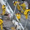 Track workers repair the safety fence along on the front grandstands, where Kyle Larson\'s car hit it on the final lap of the NASCAR Nationwide Series auto race at Daytona International Speedway in Daytona Beach, Fla., Saturday, Feb. 23, 2013. (AP Photo/Phelan M. Ebenhack)