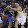 Photo - Orlando Magic guard Arron Afflalo, left, drives the ball against Golden State Warriors' Klay Thompson during the first half of an NBA basketball game Tuesday, March 18, 2014, in Oakland, Calif. (AP Photo/Ben Margot)