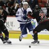 Photo - Tampa Bay Lightning's Ondrej Palat (18), of the Czech Republic, chases the puck as Carolina Hurricanes' John-Michael Liles and Patrick Dwyer (39) block during the first period of an NHL hockey game in Raleigh, N.C., Sunday, Jan. 19, 2014. (AP Photo/Gerry Broome)