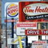 Photo - Signs for a Tim Hortons restaurant, foreground, and a Burger King restaurant are displayed along Peach Street Tuesday, Aug. 26, 2014, in Erie, Penn. Burger King struck an $11 billion deal to buy Tim Hortons that would create the world's third largest fast-food company and could make the Canadian coffee-and-doughnut chain more of a household name around the world. (AP Photo/Erie Times-News, Christopher Millette)